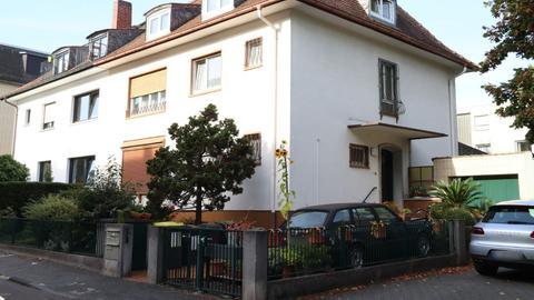 Ein Wohnhaus, vor dem zwei Autos parken.