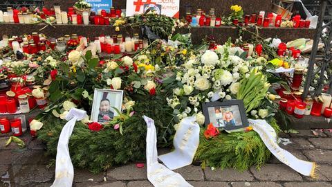 Blumen und Gestecke für die Opfer liegen auf dem Marktplatz in Hanau.