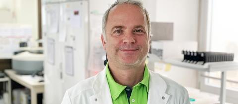 Der Virologe Martin Stürmer steht im Labor und lächelt in die Kamera.