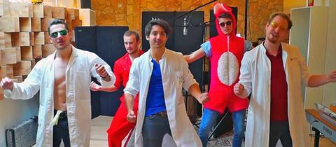 Fünf Männer tanzen mit Kittel und Kostüm bekleidet