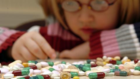 Mädchen an einem Tisch vor vielen Tabletten