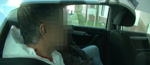 Der Verdächtige in Handschellen in einem Polizeifahrzeug