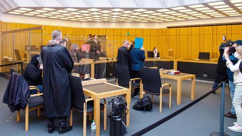 Foto der Gerichtsverhandlung. Im Gerichtssaal stehen Gerichtsbeamte und Medienvertreter.