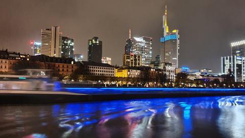 Die blauen Lichter des Frachtschiffs spiegeln sich im Main. Im Hintergrund erstreckt sich die Frankfurter Skyline. Wir danken hessenschau.de-Nutzer Sadat Demoli für das Einsenden dieses Fotos, das er am Holbeinsteg geknipst hat.