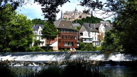 Zwei Marburger erfrischen sich an einem heißen Tag vor toller Kulisse in der Lahn.