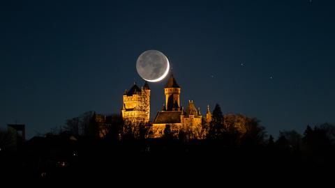 Nachtaufnahme mit beleuchtetem Schloss, darüber steht der Mond