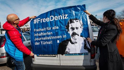"""Solidaritätsaktion für Deniz Yücel in Flörsheim: Zwei Menschen befestigen ein Plakat mit der Aufschrift """"Free Deniz"""" an einem Auto."""