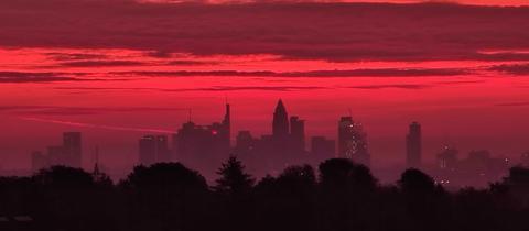 Frankfurter Skyline bei Sonnenaufgang, in rotes Licht getaucht