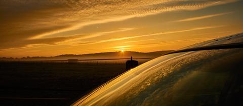 """""""Da die Sonne sich ja die nächsten Tage rar machen soll, habe ich heute morgen nochmal den tollen Sonnenaufgang fotografiert. Dabei ist ein Stückchen von meinem Auto drauf"""", schreibt uns Sabine Vogt-Hofmann aus Usingen. Haben Sie auch ein außergewöhnliches Bild aus Hessen? Dann schicken Sie uns Ihr Foto - wir freuen uns über Ihre Momentaufnahme."""
