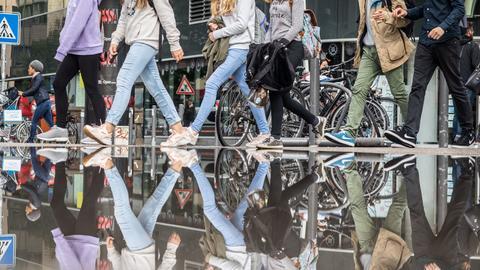 Nach dem Wolkenbruch - eine Gruppe Frankfurter Schüler geht an einer riesigen Pfütze vorbei, die sich nach Regen in der Innenstadt gebildet hat.
