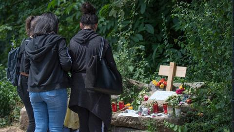 Junge Frauen legen an einer provisorischen Gedenkstätte Blumen nieder