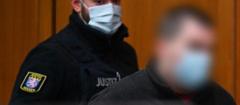 Der Angeklagte (rechts) wird zu Beginn des Mordprozesses in den Gerichtssaal geführt.