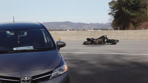 Ein Motorrad liegt auf der Autobahn, im Vordergrund ein Auto der Notfallseelsorge.