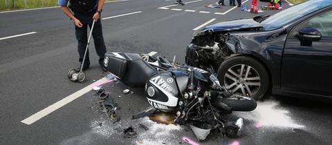 Ein Motorrad liegt vor einem Auto auf der Straße.