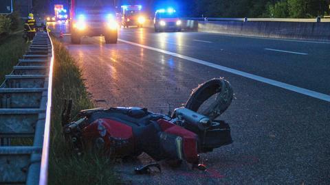 Ein gestürztes Motorrad liegt auf der Autobahn, Rettungskräfte im Hintergrund.