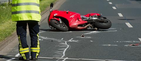 Motorrad liegt auf Straße, Mann mit Warnweste