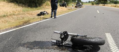 Teile des zerstörten Motorrads und ein Polizist an der Unfallstelle