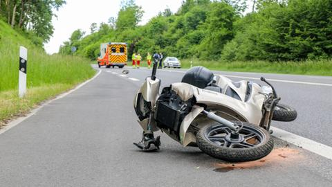 Der beschädigte Roller liegt auf der Landstraße.