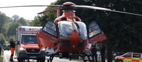 Ein Hubschrauber und mehrere Rettungswagen stehen auf der Landstraße.