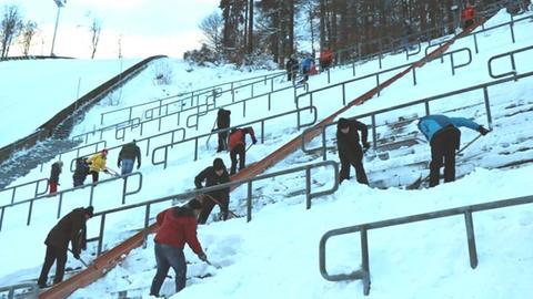 Schneeschippen auf der Tribübe der Mühlenkopfschanze in Willingen