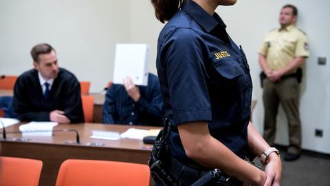 Der Angeklagte sitzt mit einem Ordner vor dem Gesicht in einem Verhandlungssaal des Münchner Landgerichts.