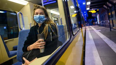 Frau mit Mundschutz in der Straßenbahn