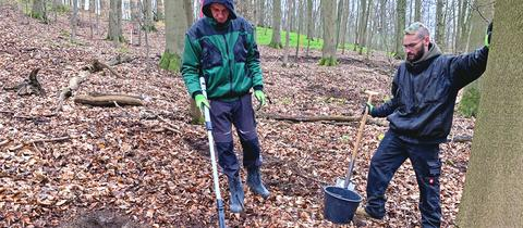 Zwei Männer mit Metallsuchgeräten im Wald