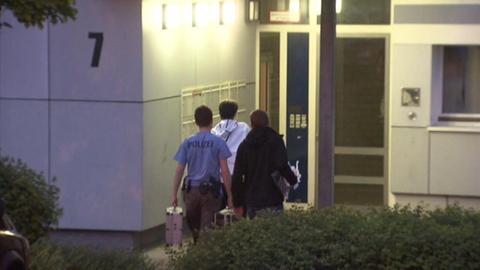 Polizisten betreten das Haus, in dem sich die Attacke ereignet hat.