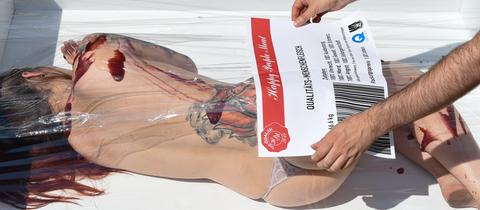 Eine Frau liegt nackt und blutig in einer überdimensionierten Verpackung.