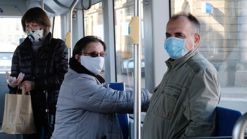 Menschen mit Mundschutz in einer Straßenbahn.
