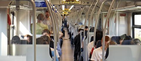 Zu sehen sind Menschen, in einem Abteil einer S-Bahn sitzend.