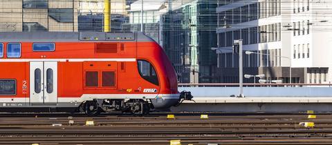 Das Foto zeigt einen Nahverkehrszug vor der Stadtkulisse Frankfurts - eingespannt zwischen Gleislinien und Oberleitungslinien.