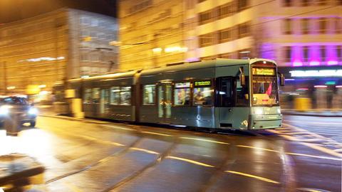 Zu sehen ist eine fahrende Straßenbahn im abendlichen Frankfurt.