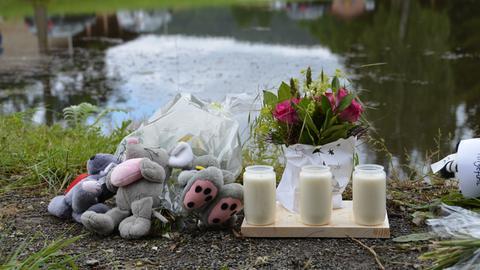 Kerzen und Kuscheltiere am Ufer des Teichs.