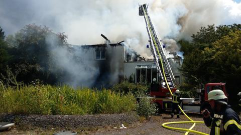 Feuerwehrleute vor der brennenden Klinik.