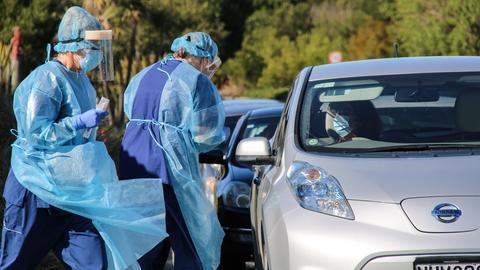 Zwei Mitarbeiterinnen in Schutzkleidung stehen neben einem Auto.