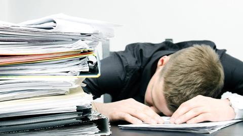 Ein Mann macht am Schreibtisch ein Nickerchen. (Archivbild)