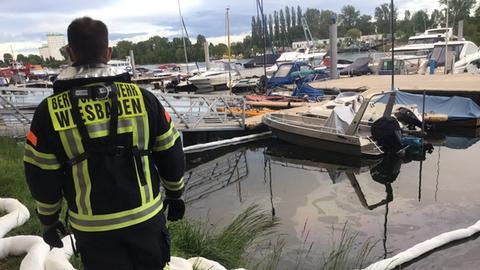 Ein Feuerwehrmann steht im Schiersteiner Hafen.