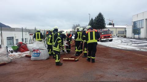 Feuerwehrleute verteilen Bindemittel aus großen Säcken