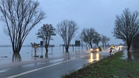 Autos fahren auf teils überschwemmter Straße