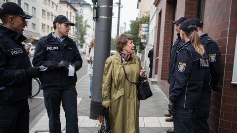 Eine Anwohnerin beschwert sich bei Polizisten über den Ausfall der Straßenbahnen. Sie muss deswegen mehrere Kilometer zu Fuß gehen.