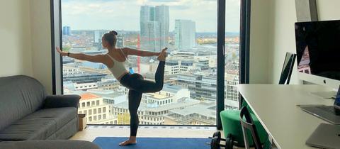 Eine Bewohnerin des sogenannten Omniturms in Frankfurt macht Yoga in ihrer Wohnung - mit Blick auf Frankfurt.