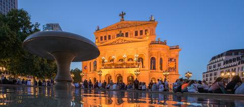 Menschen sitzen auf dem dem Beckenrand des Lucae-Brunnen auf dem Opernplatz.