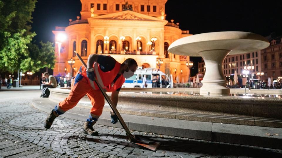 Ein Mitarbeiter der Stadtreinigung entfernt mit einer Schaufel Abfall vor der Alten Oper, nachdem Besucher den Platz verlassen mussten.