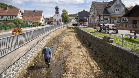 """Mit einem Stock in der Hand watet ein Mann durch das etwa knietiefe Wasser der """"Bleiche"""" in Ortenberg. Hier hatte ein Bewohner des Ortes nach eigenen Angaben ein Krokodil entdeckt"""