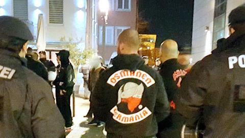 """Ein Mann mit """"Osmanen-Germania""""-Kapuzenpulli neben zwei Polizisten."""