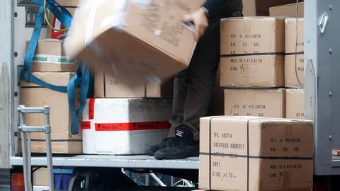 Ein Mann räumt Pakete aus einem Lastwagen.