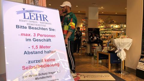 Hinweisschild zum Coronavirus vor einer Frankfurter Parfümerie