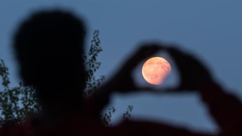 Ein Mann visiert in Frankfurt mit seinen Händen eine partielle Mondfinsternis an, die er am Bornheimer Hang verfolgt.
