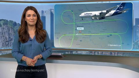 Standbild aus der Sendung hessenschau kompakt. Die Moderatorin steht vor der Hintergrundgrafik, die ein Flugzeug und die peniszeichenförmige Flugspur über Bremen zeigt.